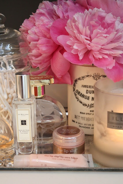 The glow of the candle and the peonies in a vintage jar are perfection